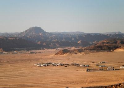 """Die moderne Siedlung Mrayhle - In den modernen Beduinensiedlungen in der Wüste sieht man oft die weißen Einheitshäuser, die vom """"World Food Programme"""" gestiftet wurden. Das Gebäude rechts im Bild ist die staatliche Schule."""