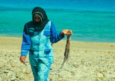 Erfolgreiche Fischerin - Während die Männer mit Hilfe von Booten und Netzen Fische fangen, suchen die Frauen in Ufernähe nach Muscheln und Tintenfischen. Getrocknet sind die Fische monatelang haltbar.