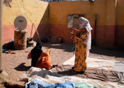 Zelt nähen und Vorfreude - Im Hof ihres Hauses in der Stadt nähen diese Mutter und ihre Tochter Mehlsäcke und Stoffplanen zusammen. Es hat geregnet und in der Wüste gibt es gutes Weideland. Sie freuen sich darauf, mit ihrer kleinen Herde für einige Wochen hinaus zu ziehen wie in den alten Zeiten.